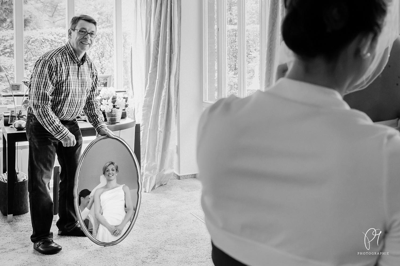 Der Brautvater hält einen Spiegel, damit sich die Braut betrachten kann.