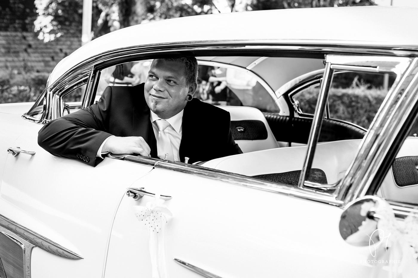 Ein Bräutigam schaut aus dem Hochzeitsauto heraus. Dieses schwarzweiss Foto stammt aus einer Hochzeitsreportage aus Haan. Aufgonommen wurde dieses Hochzeitsfoto mit der Canon 5D und mit Lightroom bearbeitet.