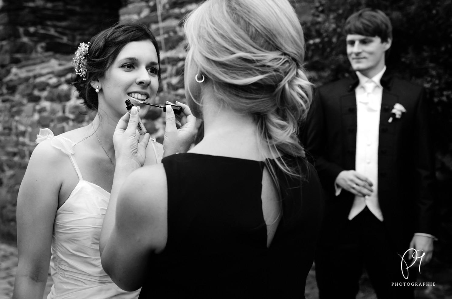 Die Schwiegermutter trägt der Braut noch etwas Lippenstift auf. Diese Aufnahme ist Teil einer Hochzeitsreportage aus Solingen und wurde auf Schloss Burg aufgenommen. Der Hochzeitsfotograf benutzte eine Canon 5D MarkIII für die Hochzeitsfotos.