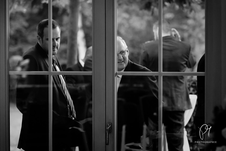Dieses Foto wurde im Gasthaus Driland aufgenommen und stammt von einer Hochzeitsreportage. Es zeigt Hochzeitsgäste, die von aussen durch ein Fensten schauen. Aufgenommen wurde dieses schwarzweiss Hochzeitsfoto mit der Canon 5D Mark III