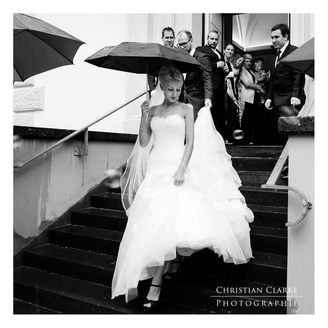 Eine Braut mit verlässt nach einer Trauung die evangelische Kirche in Solingen Wald. Da es regnet, hält sie einen Regenschirm. Aufgenommen wurde dieses Hochzeitsfoto mit der Canon 5D Mark IV.