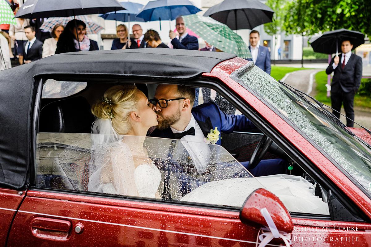 Nach der Trauung in der evengelischen Kirche Solingen Wald küsst sich ein Brautpaar im Auto. Im Hintergrund stehen die Gäste mit Regenschirmen.