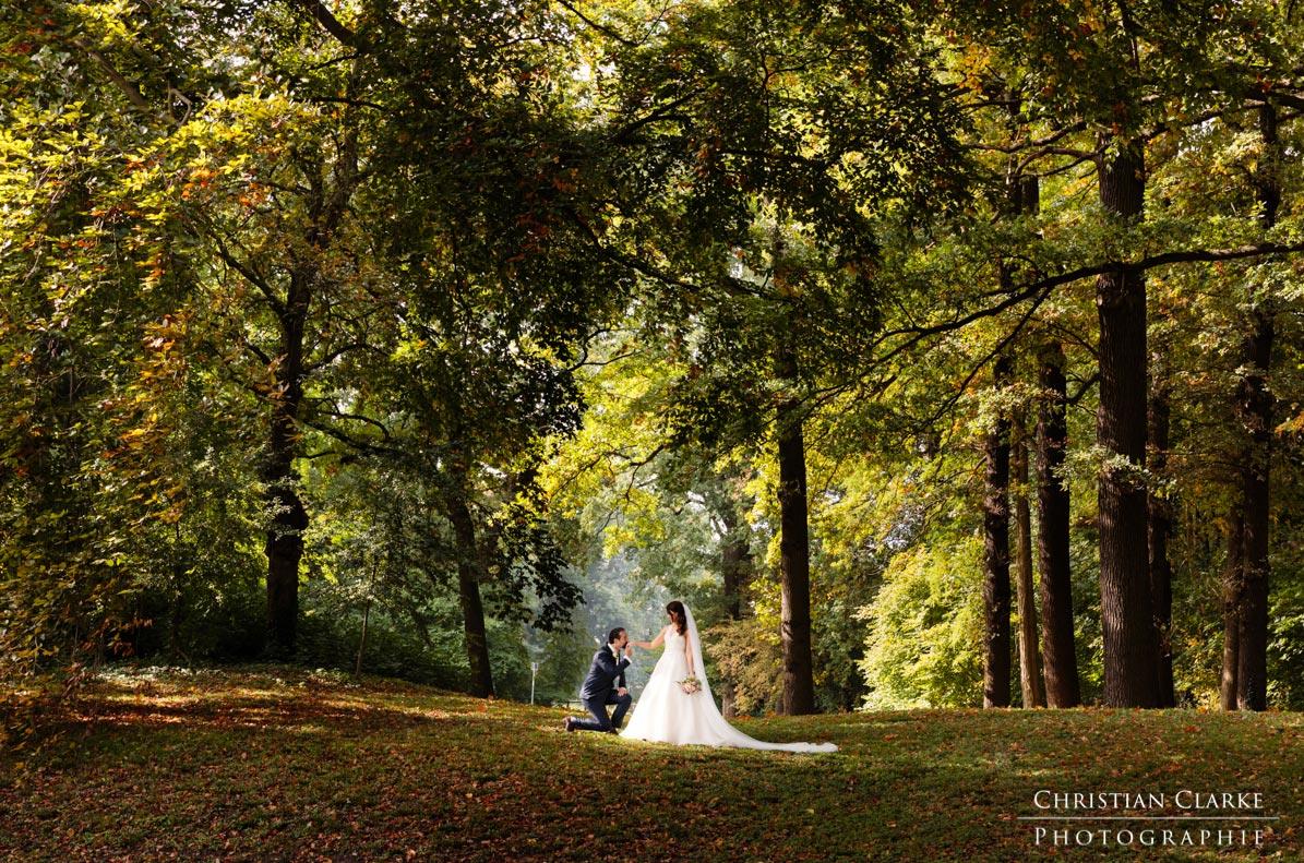 Eine Hochzeit im Oktober.Ein Brautpaar steht auf einer Lichtung. Der Bräutigam kniet vor der Braut. Dieses Hochzeitsfoto wurde auf dem Geläde der Burg Bergerhausen in Kerpen-Bergerhausen aufgenommen.